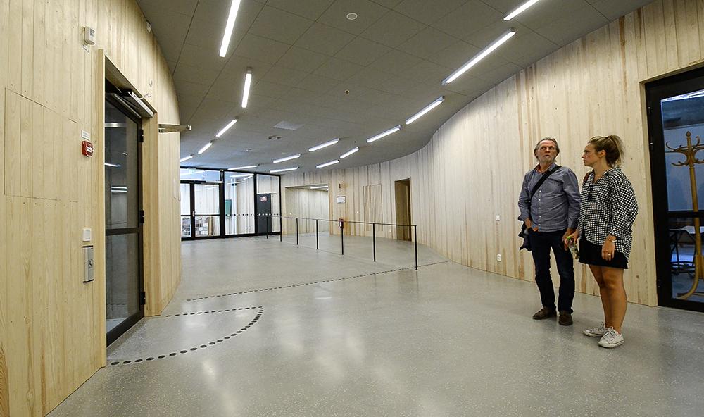 Två personer står och lyssnar i en korridor med lysrör i taket. Jonas Dahlberg An imagined city