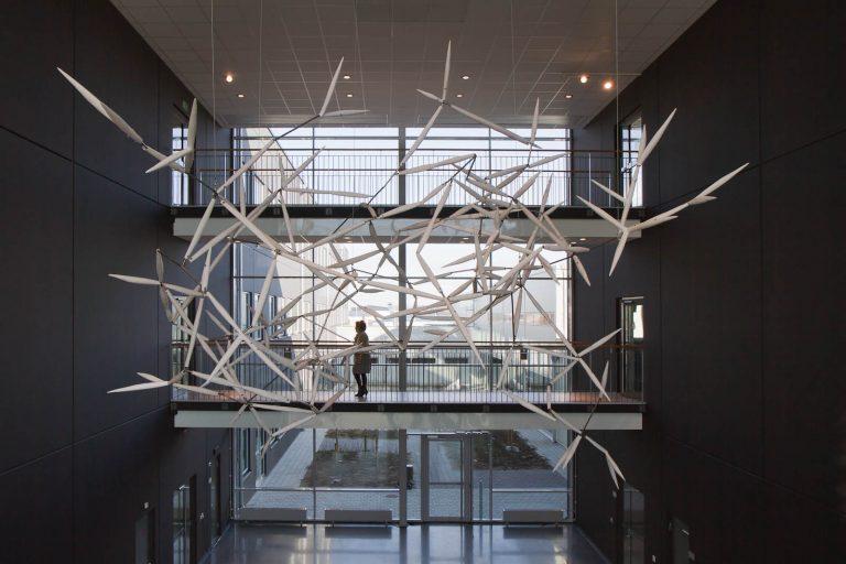 Keramiska verket Luftkropp svävar högt uppe vid taket i en ljusgård, bredvid en loftgång.