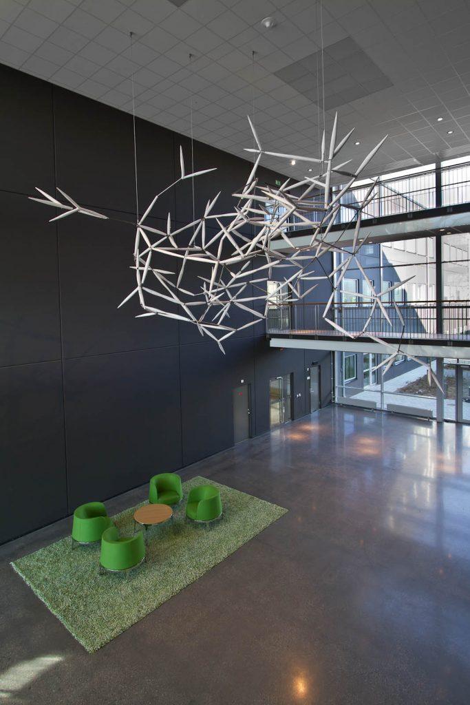 Verket Luftkropp, bestående av sammanfogade vita spiror, svävar högt uppe vid taket i en ljusgård. Karin Jaxelius
