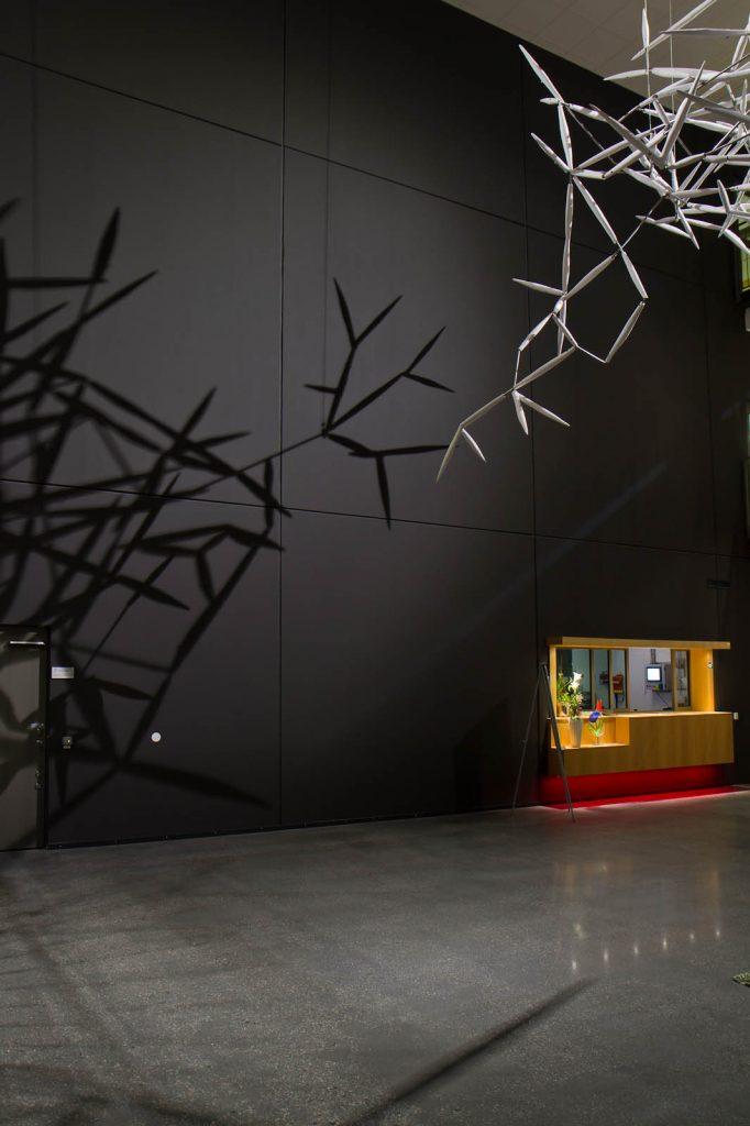 På kvällen i lampornas sken kastar verket Luftkropp ett virrvarr av skuggor på den mörka väggen bredvid receptionsdisken. Karin Jaxelius