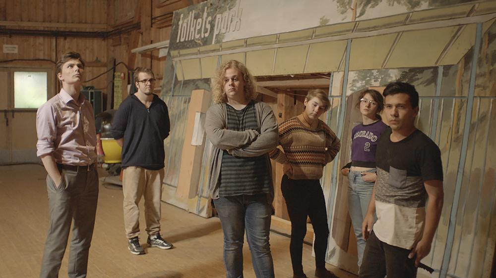 Fyra män och två kvinnor står och hänger och tittar ointresserat i olika riktningar. I bakgrunden en teaterkuliss med texten: