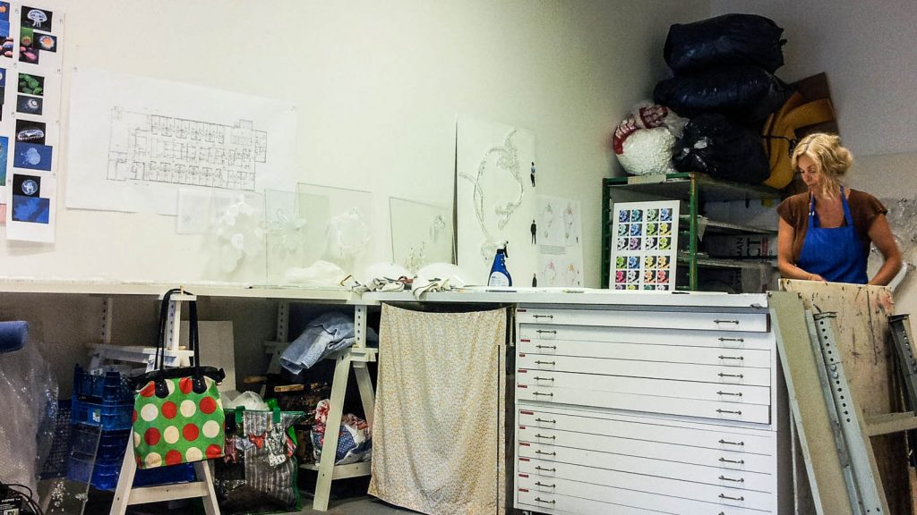 I ateljén. Skisser på väggen. Konstnären Fredrika Linder i skyddsförkläde jobbar vid en arbetsbänk. Fredrika Linder, W
