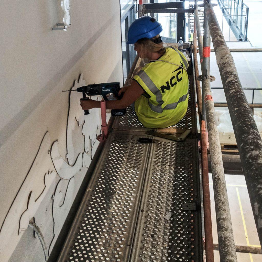 Konstnären i reflexväst och hjälm på en byggställning borrar hål i väggen med utgångspunkt i de utskurna pappschablonerna. Fredrika Linder, W