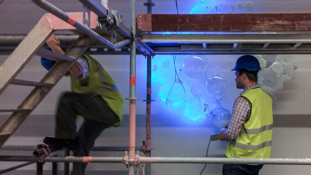 En man i reflexväst testar den turkosskimrande belysningen från en glasformation på väggen. Fredrika Linder, W