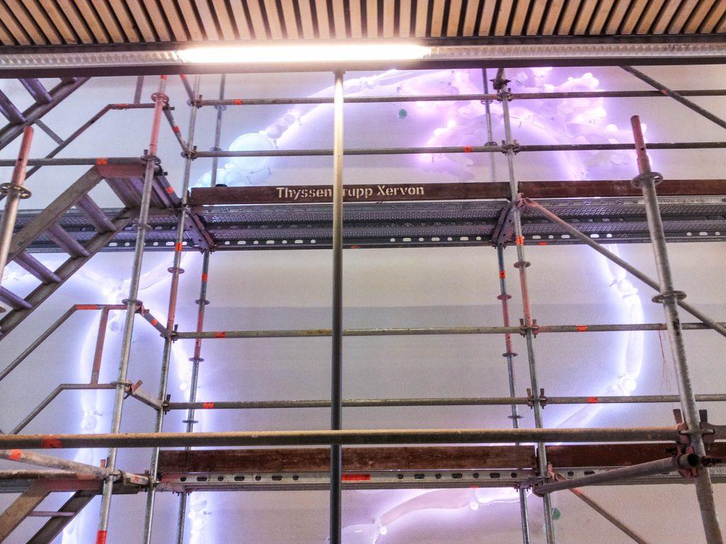 På väggen bakom en hög byggställning lyser en organisk kontur i vitt och skärt. Fredrika Linder, W