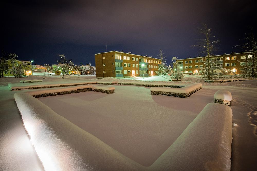 Nattbild med upplysta tegelbostadshus och trävillor i bakgrunden och låga snötäckta gabioner fyllda med rivningsmassor i förgrunden. Sofia Sundberg, Karl Tuikkanen, Ingo Vetter, Gruvstadsparken.