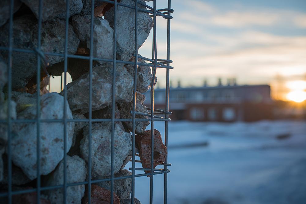 Detalj, gabion fylld med rivningsmassor. I bakgrunden ett hus. Sofia Sundberg, Karl Tuikkanen, Ingo Vetter, Gruvstadsparken.