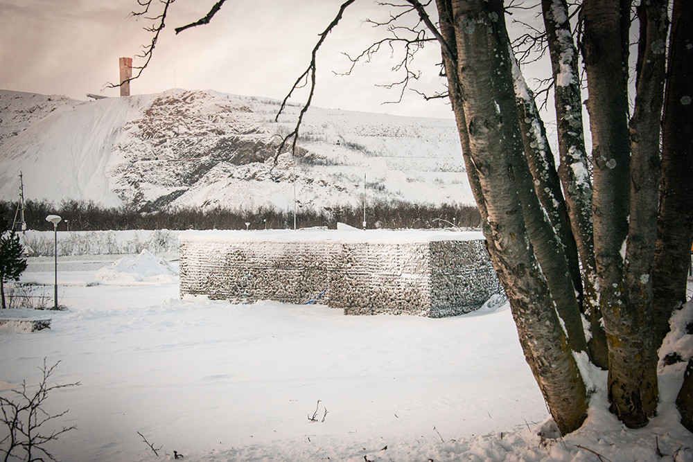 Gabioner, ett slags stora stålkorgar, fyllda med krossat tegel och betong från rivna hus. I bakgrunden en kulle, i förgrunden träd. Sofia Sundberg, Karl Tuikkanen, Ingo Vetter, Gruvstadsparken.