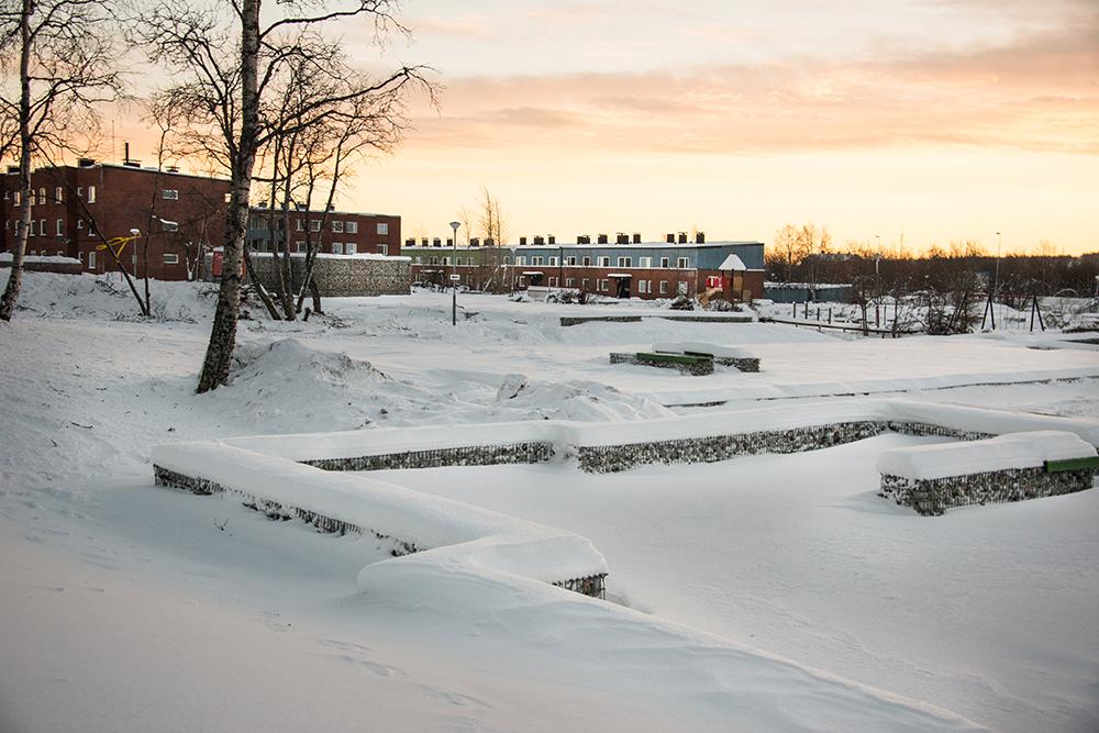 Gabioner, ett slags stora stålkorgar, fyllda med krossat tegel och betong från rivna hus. I bakgrunden två intakta bostadshus. Sofia Sundberg, Karl Tuikkanen, Ingo Vetter, Gruvstadsparken.