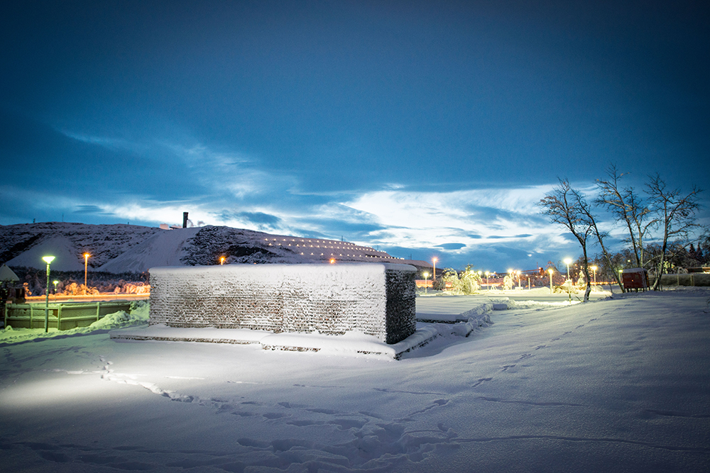 Snölandskap upplyst av gatlyktor med mörk himmel och i mitten snötäckta gabioner med rivningsmassor. Sofia Sundberg, Karl Tuikkanen, Ingo Vetter, Gruvstadsparken.