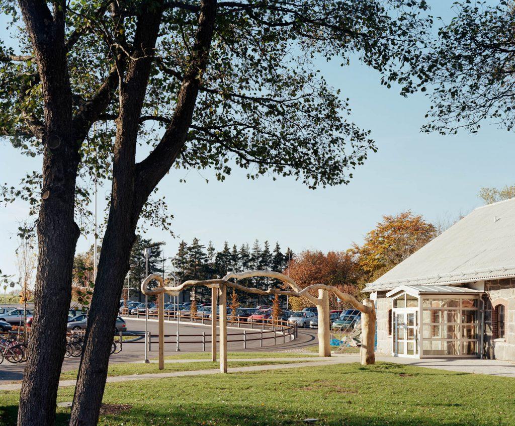 Två höga stubbar med en lång gemensam gren, på stöttor, utanför skolingången. Malin Bogholt, Kontakt