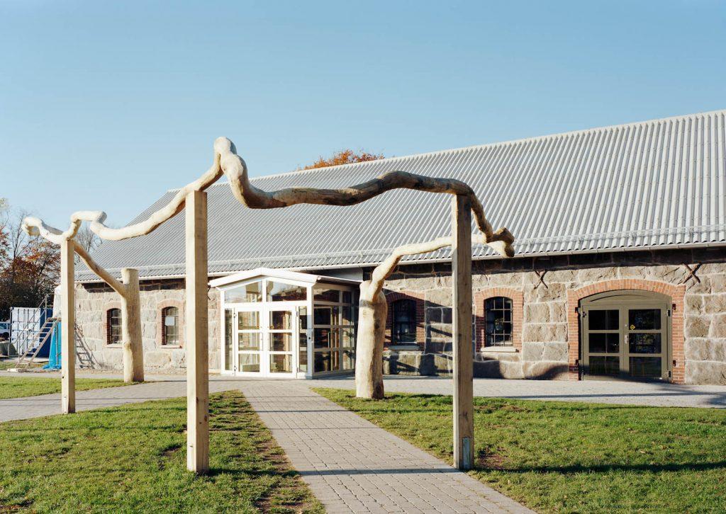 Grenen slingrar sig i en stor halvcirkel. Mellan stöttorna leder två gångvägar fram till skolporten. Malin Bogholt, Kontakt