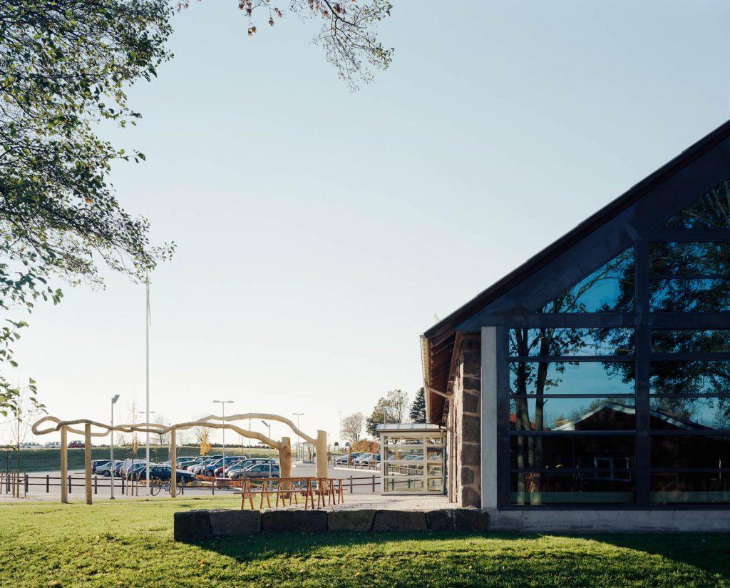Vid sidan av verket, på byggnadens solsida, står trästolar och bord. Malin Bogholt, Kontakt