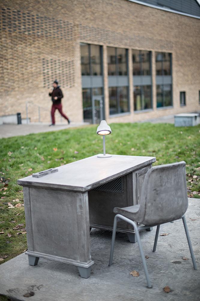 Bredvid sängen står ett skrivbord med en stol och en lysande lampa, allt gjutet i betong. Mandana Moghaddam, Vinden bär oss med sig