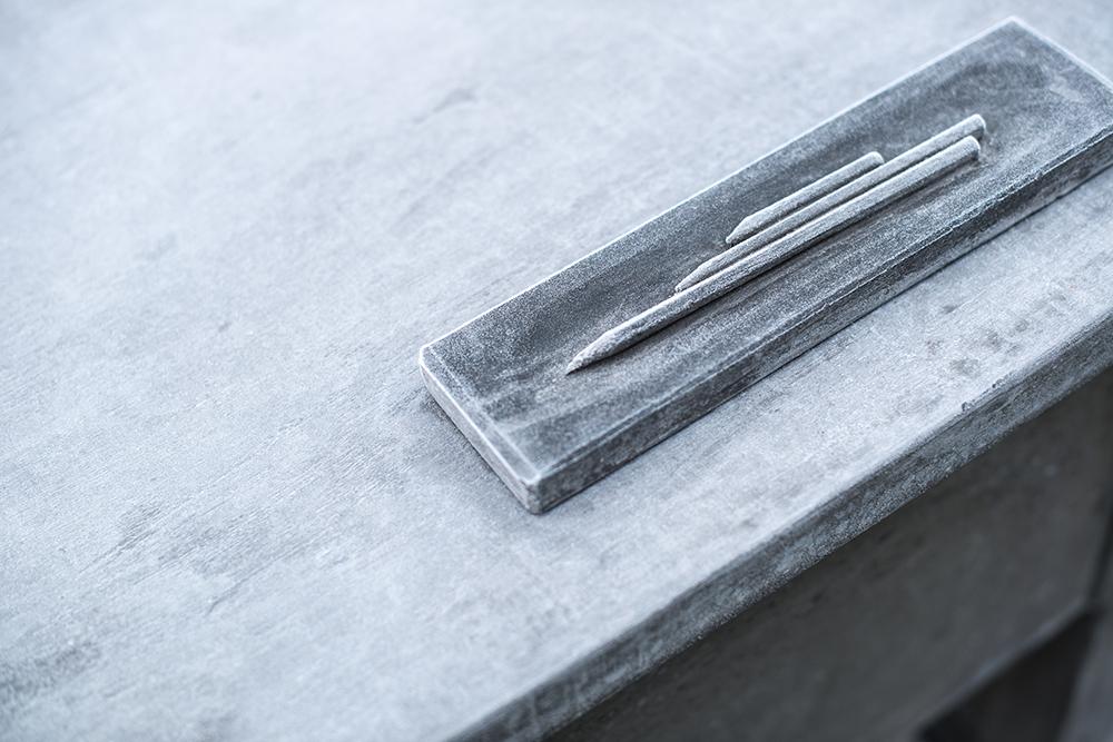 På skrivbordet av betong ligger tre pennor i en pennhållare av betong. Mandana Moghaddam, Vinden bär oss med sig