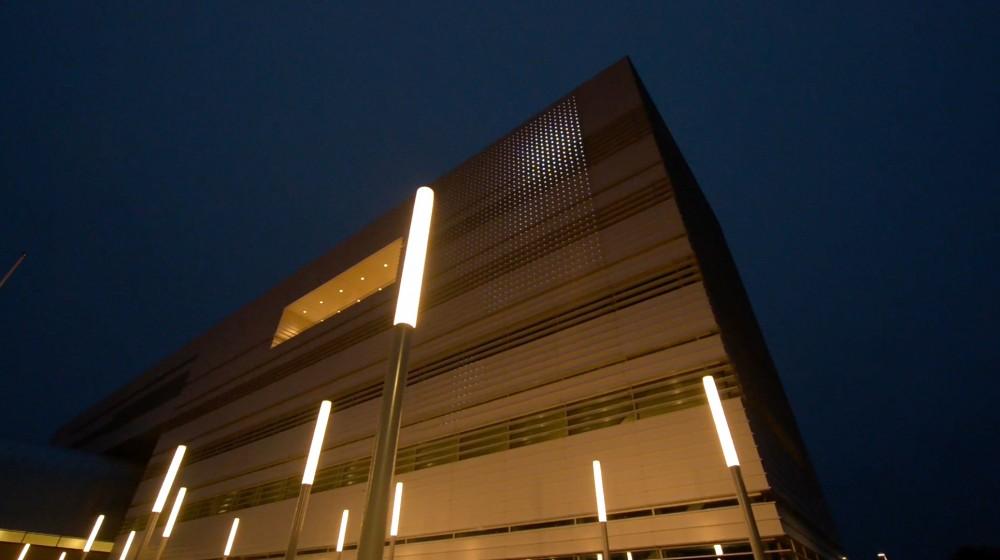 Vit fasad i gatlyktors sken. På fasaden en ljusprojicering. Lina Selander, Mehr Licht!