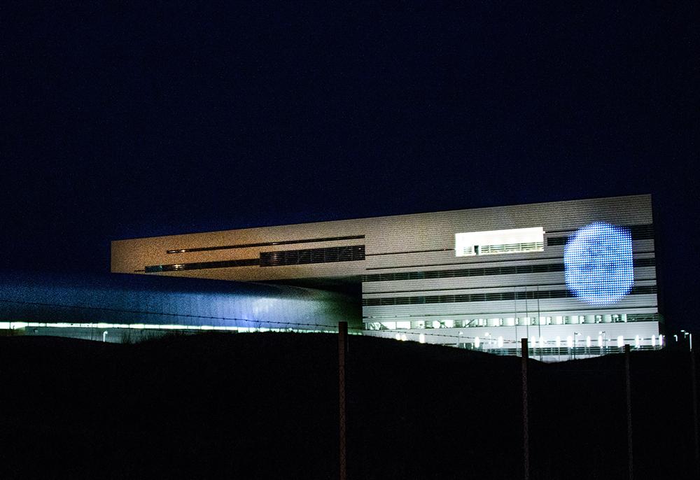 Flervåningshus i nattmörker. På sidan av fasaden projiceras bilden av en planet. Lina Selander, Mehr Licht!