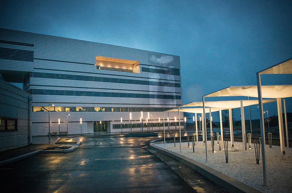 Regnvåt asfalt, cykelställ och modernt flervåningshus med en ljusprojicering på fasaden. Lina Selander, Mehr Licht!