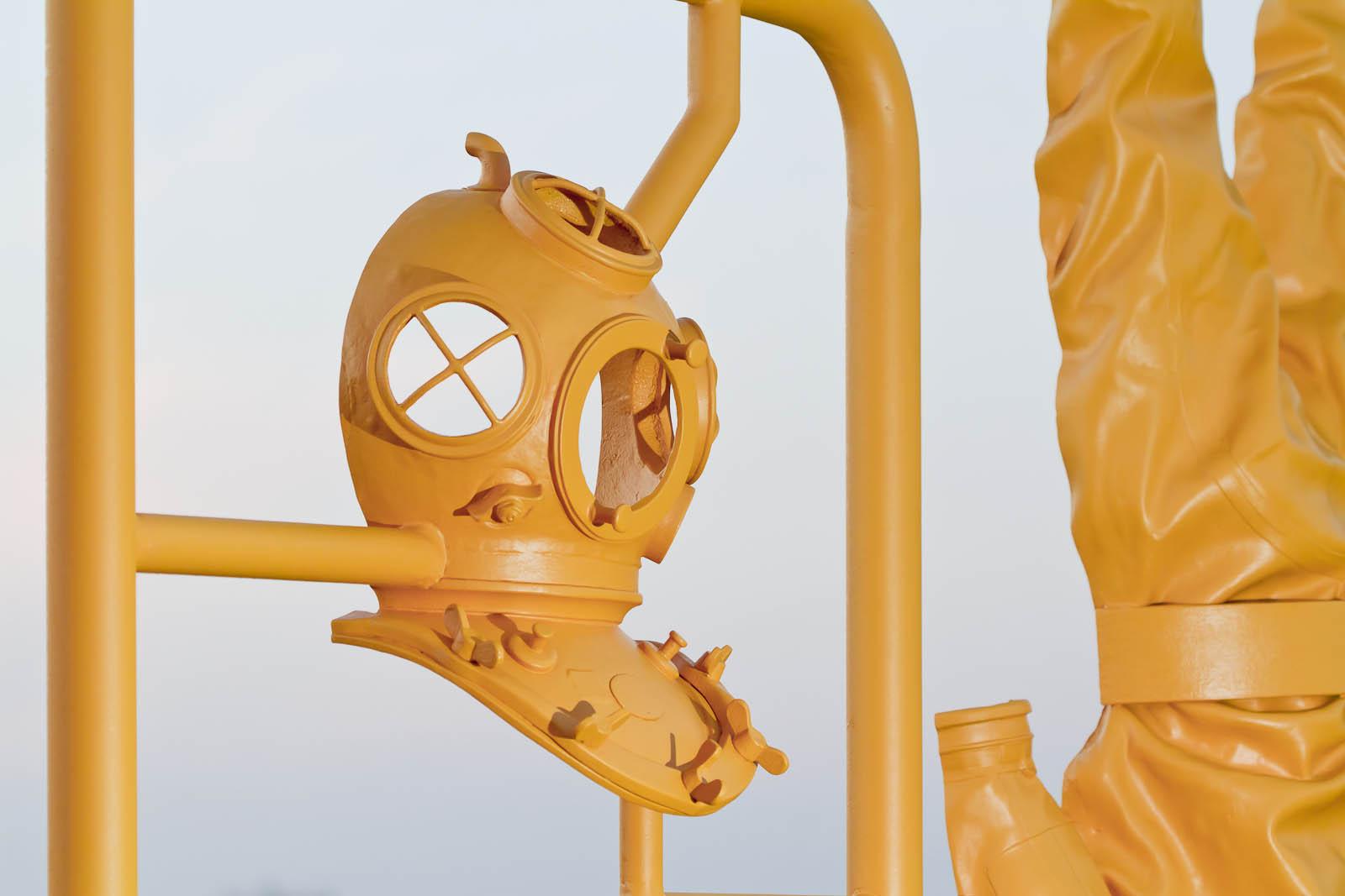 Främre hälften av en gammaldags dykarhjälm, i gul plast. Del av en modellbyggsats i skala 1:1. Michael Johansson, Some Assembly Required - Hard Hat Diving
