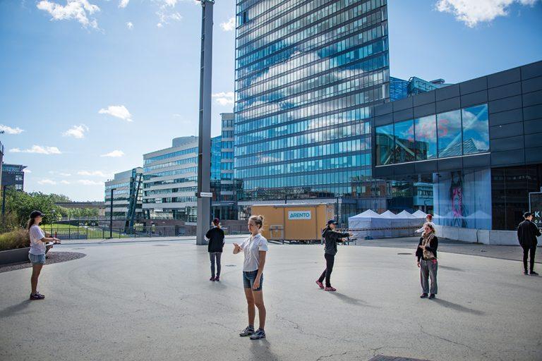 En grupp personer står utomhus vända åt olika håll med ena armen lyftad. Arbetets monument Alexandra Pirici