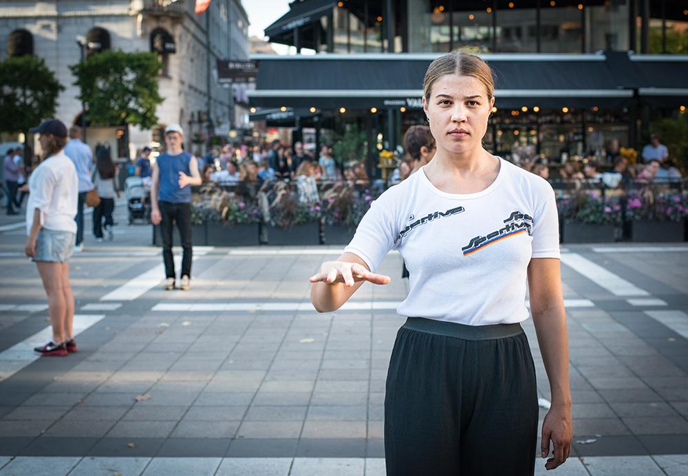 En ung kvinna med armen framsträckt och fingrarna utspärrade. I bakgrunden en restaurang med fullsatt uteservering. Arbetets monument Alexandra Pirici