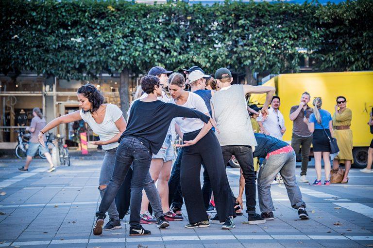 En grupp personer står böjda åt olika håll i färd med olika rörelser. I bakgrunden människor som tittar. Arbetets monument Alexandra Pirici