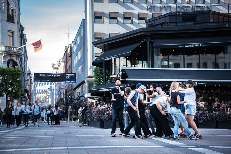 En klunga människor gör olika armrörelser på en stadsgata. Arbetets monument Alexandra Pirici