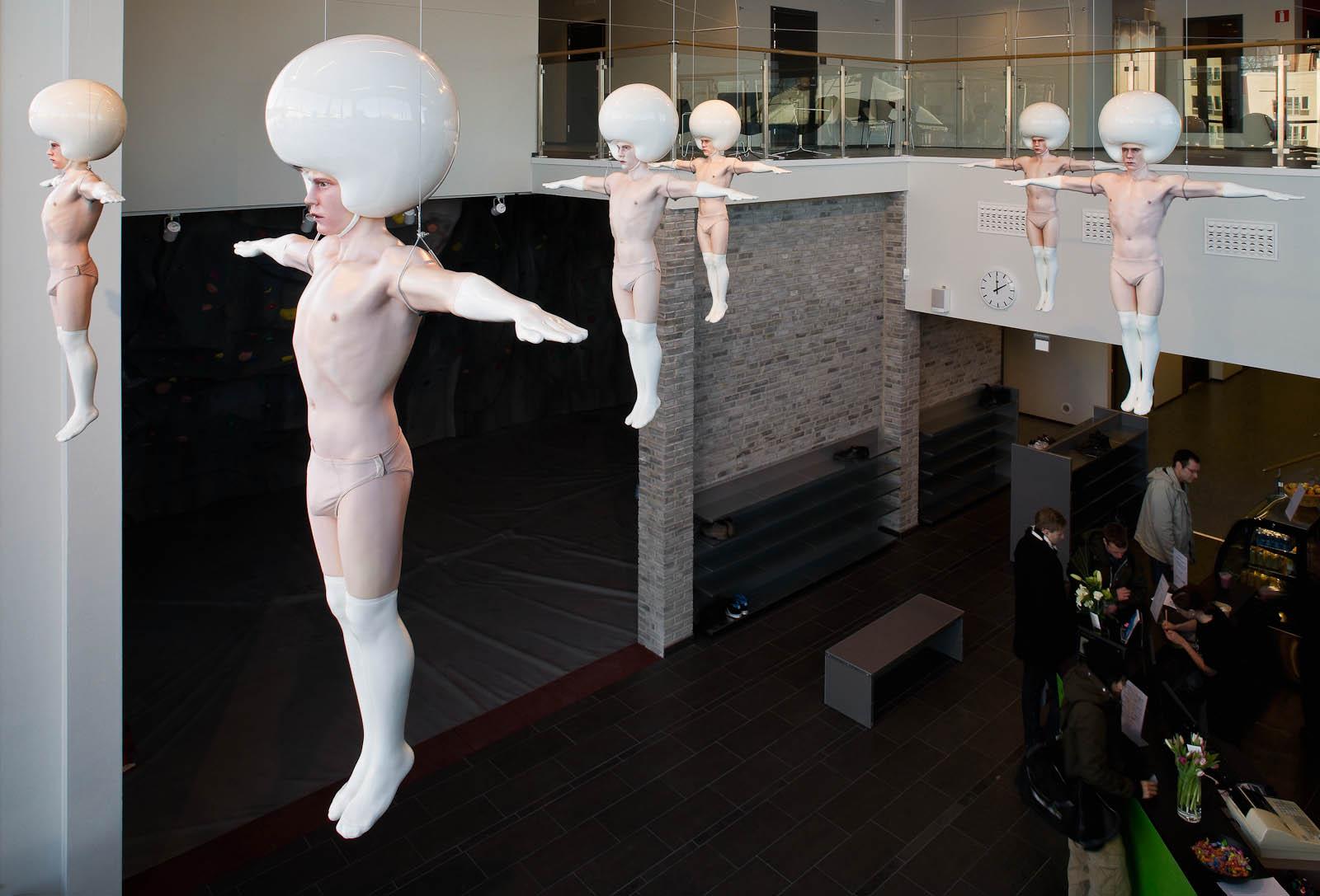 Nedanför de upphängda skulpturerna finns en kafeteria där personer handlar. Christian Pontus Andersson, A Joyful Troop of Perfection, with crying sensitive hearts