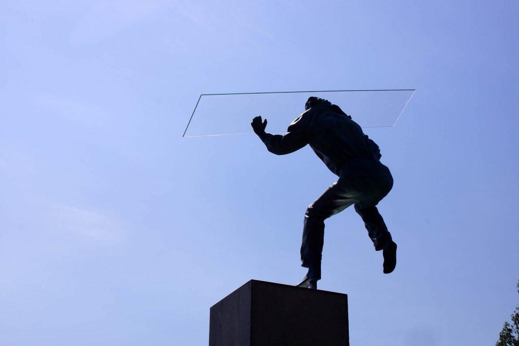 Skulpturens armar är höjda, på handflatorna balanserar han en glasskiva. Heinrich Müllner, Flyer, 2014
