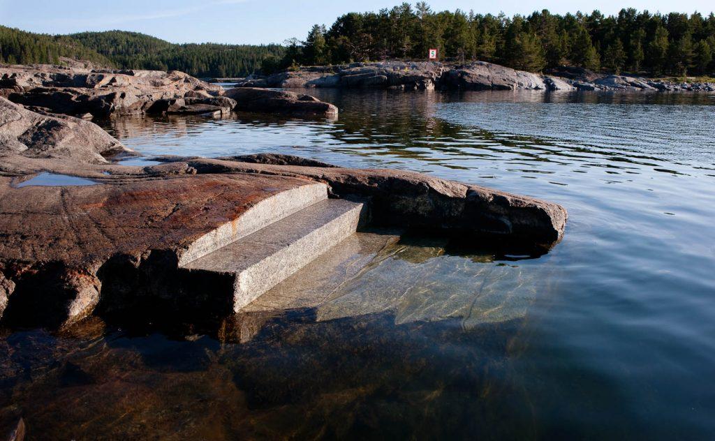 Fem breda trappsteg inhuggna i klippstranden. De fyra nedre är täckta av vattnet och skymtar genom dess skiftningar. Katarina Löfström, Passage