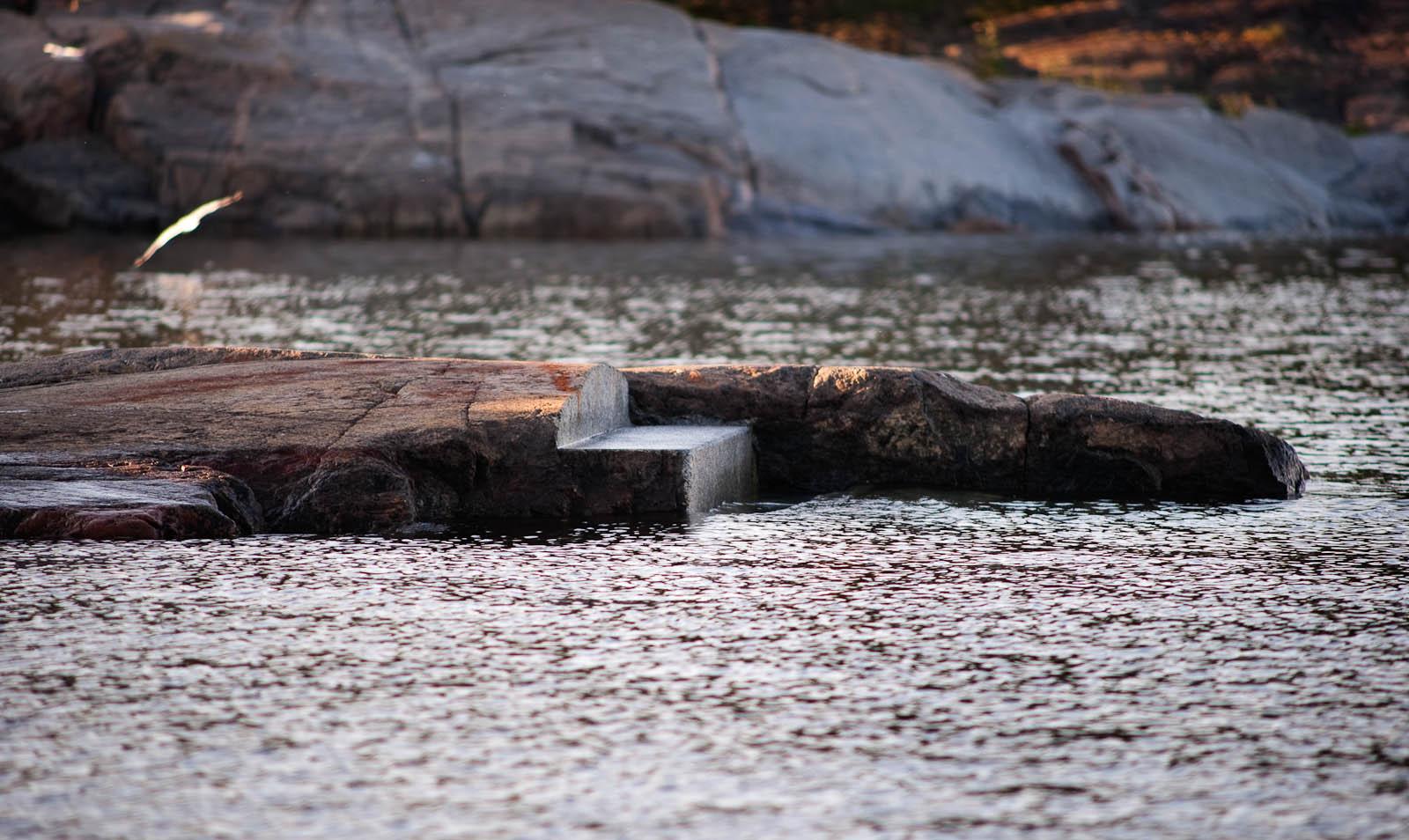 Strömmande ogenomskinligt vatten. Ett trappsteg inhugget i klippan, som leder ner i vattnet. I bakgrunden flyger en fågel. Katarina Löfström, Passage