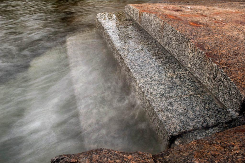Inhuggna trappsteg i klippan vid vattenbrynet. Över de nedre trappstegen forsar och skummar vattnet. Katarina Löfström, Passage