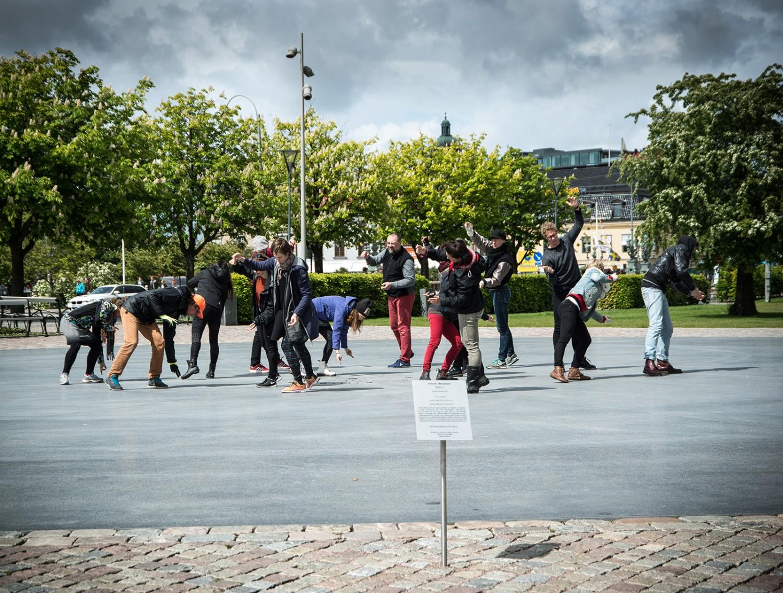 En grupp personer på en öppen plats. Alla står böjda åt olika håll och tycks vara i rörelse. Arbetets monument Alexandra Pirici