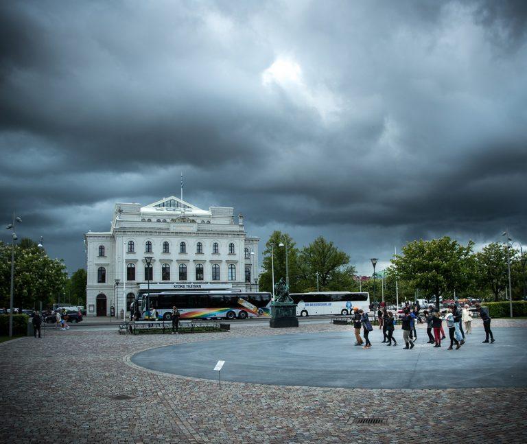 Hotfulla regnmoln över Stora Teatern i Malmö. En grupp personer i hörnet av bilden gör armrörelser. Arbetets monument Alexandra Pirici