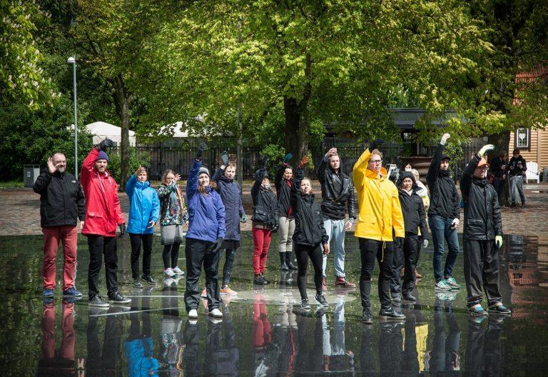 En stor grupp personer klädda i ytterkläder står med högerarmarna uppsträckta. Arbetets monument Alexandra Pirici