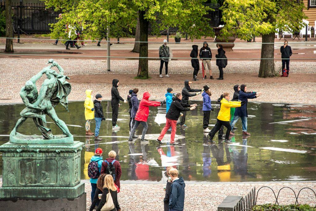 En klunga människor i regnkläder på ett torg står med armarna framsträckta. Människor tittar i bakgrunden. Arbetets monument Alexandra Pirici