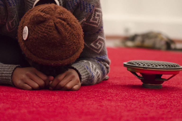 En person i kofta och mössa ligger framåtböjd på en röd matta bredvid en högtalare. James Webb, Prayer (Malmö).