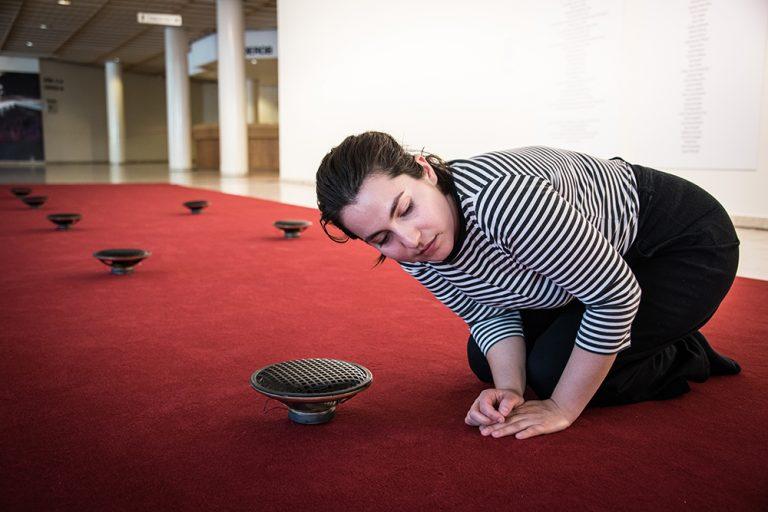 En kvinna sitter hopkrupen på en röd matta och lyssnar på ljudet från en av flera högtalare som finns utplacerade. James Webb, Prayer (Malmö)