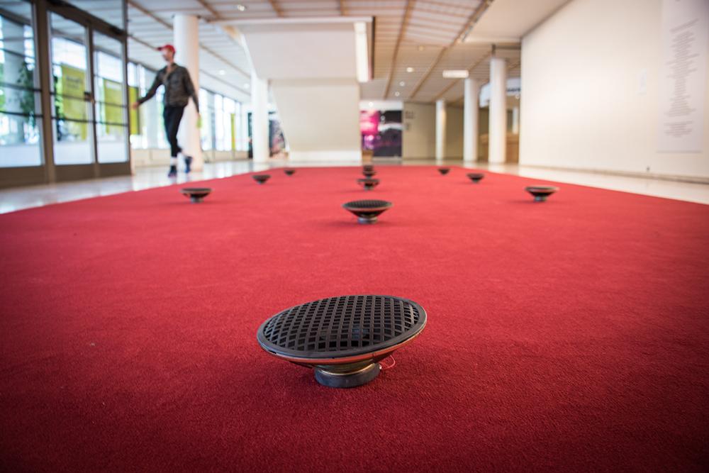 På en avlång röd matta i en vestibul ligger svarta högtalare utplacerade. James Webb, Prayer (Malmö)