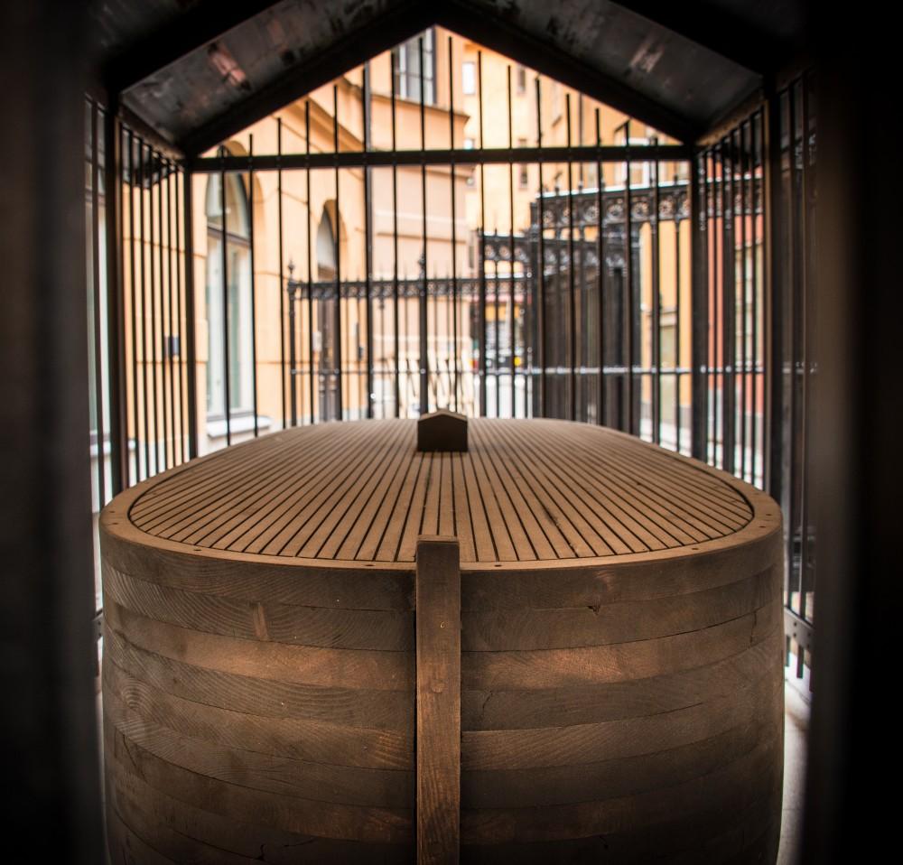 En övertäckt träbåt innanför ett galler. Jan Håfström Arken