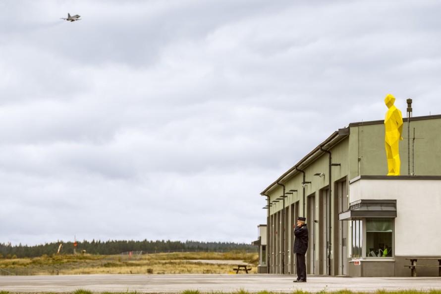 Knallgul skulptur av en man på taket av en byggnad. Xavier Veilhan, Julian.