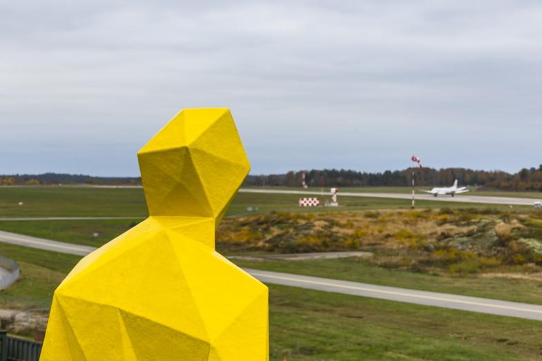 Gul skulptur av en man som blickar ut över ett flygfält, detalj. Xavier Veilhan, Julian.