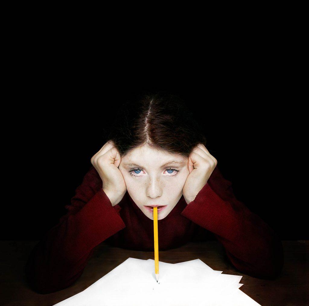 Fotografi. En flickas belysta ansikte. Hon lutar huvudet i händerna med tom blick. Läpparna balanserar en penna mot ett vitt papper. Julia Peirone, Sharphead