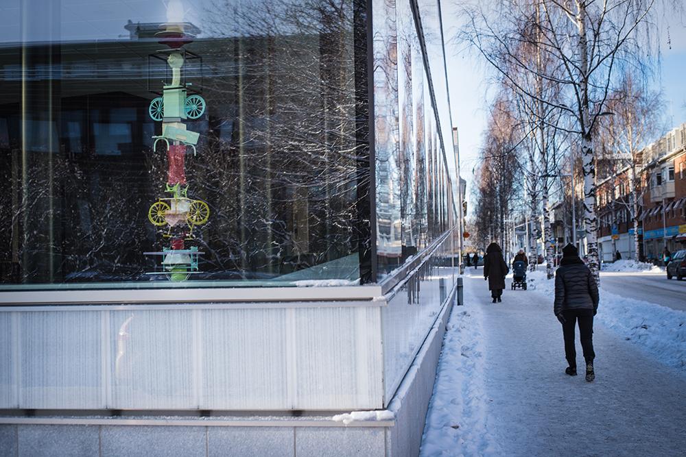 Människor går i snön längs gatan. Genom fönstret syns pelaren av udda föremål. Sirous Namazi, Rekonstruktion