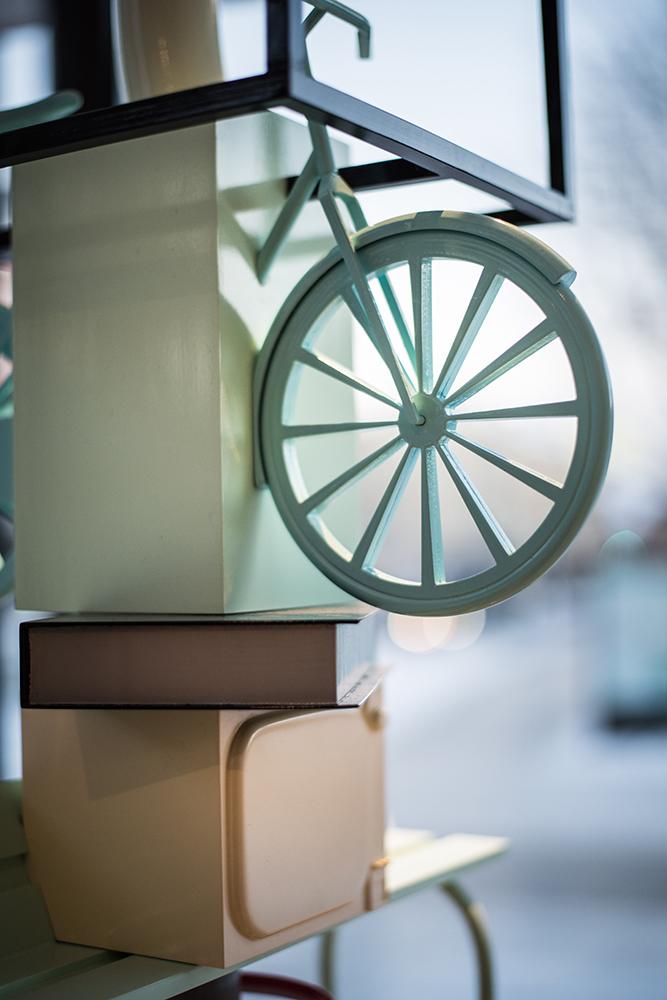 Detalj. I pelaren ingår en liten grön cykel ovanpå en liten bok. Sirous Namazi, Rekonstruktion