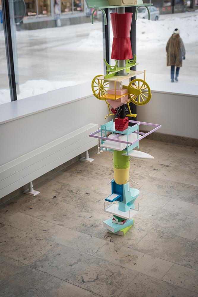 Verkets bas består av staplade, olikfärgade hinkar, en toalettstol, en strykbräda, en våningsäng. Sirous Namazi, Rekonstruktion