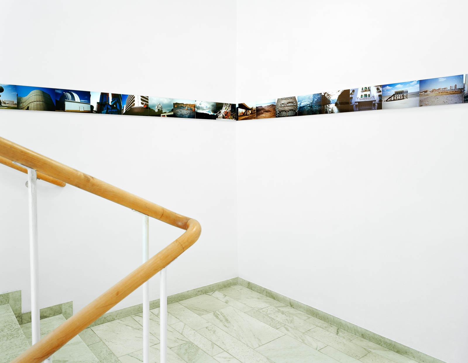 Vitmålat trapphus med en smal bård av fotografier från olika platser som följer väggen. Franz Ackermann, Travelling North, (2007).