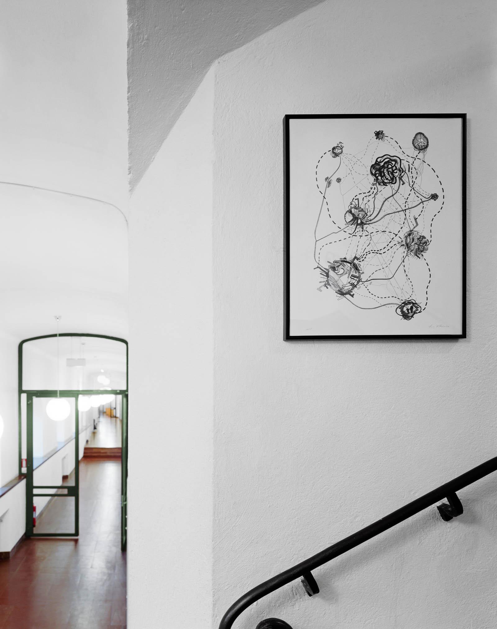 Svartvitt inramat verk på väggen i ett trapphus. Celliknande former sammanlänkade av streckade linjer. Franz Ackermann, Travelling North, (2007).