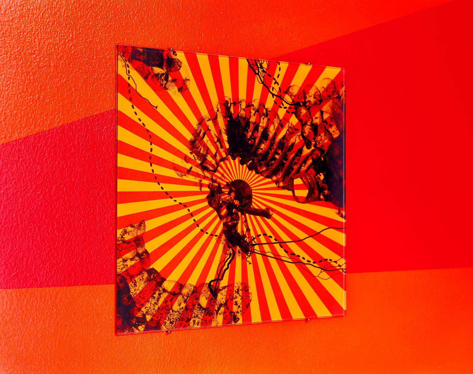 Rödgul väggmålning med dödskallar på röd grund. Franz Ackermann, Travelling North, (2007).