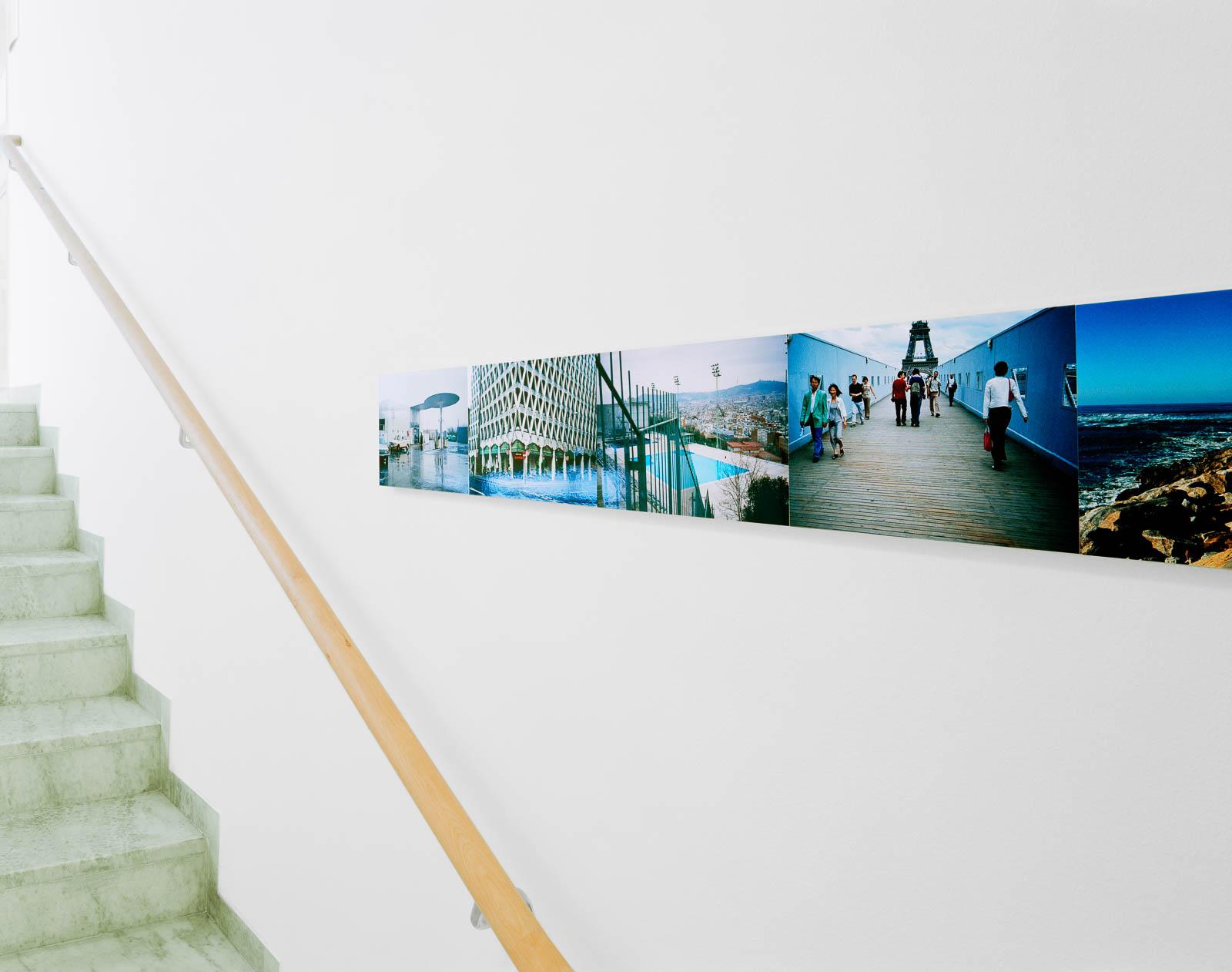Del av sammanhängande fotoserie i trapphus. På en bild skymtar Eiffeltornet, på en annan en inhägnad badbassäng och ett mycket högt hus. Franz Ackermann, Travelling North, (2007).